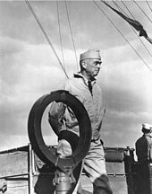 A man wearing a garrison cap and windbreaker paces on the deck of a ship.