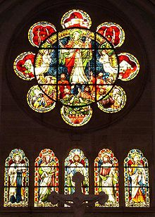 A rose window of simple form having a circle with eight lobes like a flower. It has glass showing Christ rising into heaven watched by apostles and angels. Below are five arched windows each with a saint. Red and yellow are the predominant colours
