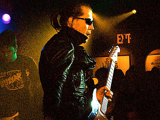 "Garage rock - Link Wray, pictured in 1993, who helped pioneer the use of guitar power chords and distortion as early as 1958 with the instrumental, ""Rumble"", has been cited as an early influence on garage rock."