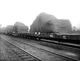Flatcar - A string of flatcars carries tanks (under tarps) in April 1943
