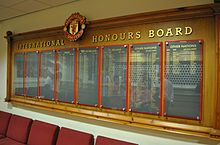 "A wooden board headed with the Manchester United crest and the words ""International Honours Board"", with names in gold writing on eight slate panels, protected by perspex panels."
