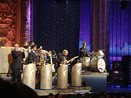 "Several men are playing instruments, including trumpet, saxophone, trombone, and guitar, behind bandstands; at a higher elevation to the right of them is another man behind a drum kit and looking over at the band members; the bass drum is labeled ""The Max Weinberg 7""; behind all of them is a paster sculpture wall and a series of vertical curtains, some translucent with a painted cityscape behind them"