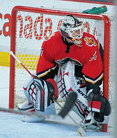 A goaltender in a red uniform and standing in front of his net observes the actions of other players (not seen).