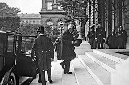 Zwart-witfoto van een besnorde, witharige man die uit een auto stapt en de trappen van een gebouw oploopt, met zijn hoed in zijn rechterhand, onder de lens van een fotograaf en de blik van andere individuen