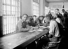 Black and white image of several prisoners, mostly of African heritage, sitting at a desk and writing. There are bars on the windows.