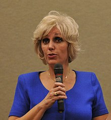 A photograph of a blond-haired, brown-eyed, middle-aged woman in a blue blouse holding a microphone.