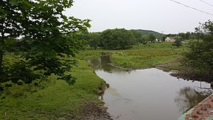 Papakating Creek in Wantage Township, New Jersey, US, a small stream flowing through green farm pastureland