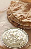 A bean dip prepared with white beans and Parmesan cheese, served with pita bread