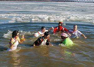 Polar bear plunge - Participants in the water during a polar bear plunge. Note the ice on the water.