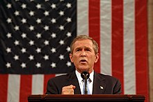 President Bush delivering a speech in front of  the American flag