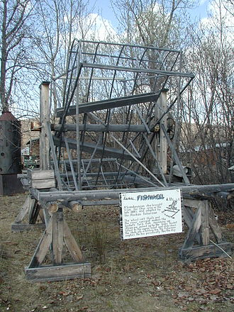 Fish wheel - Fish wheel on display in Alaska. The sign reads that fish wheels originated in Scandinavia and were brought to Alaska by a man from Ohio in the late 1800s, but there is still debate over the wheel's origins