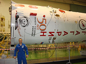 Soyuz TMA-21 - Garan stands in front of the Soyuz booster which bears the name and likeness of Yuri Gagarin.