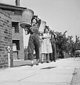 Salvage workers from the Women's Voluntary Sservice (WVS) in East Barnet, Hertfordshire, during 1943, carrying bins containing kitchen scraps that will be distributed to local farmers as food for pigs D14251.jpg