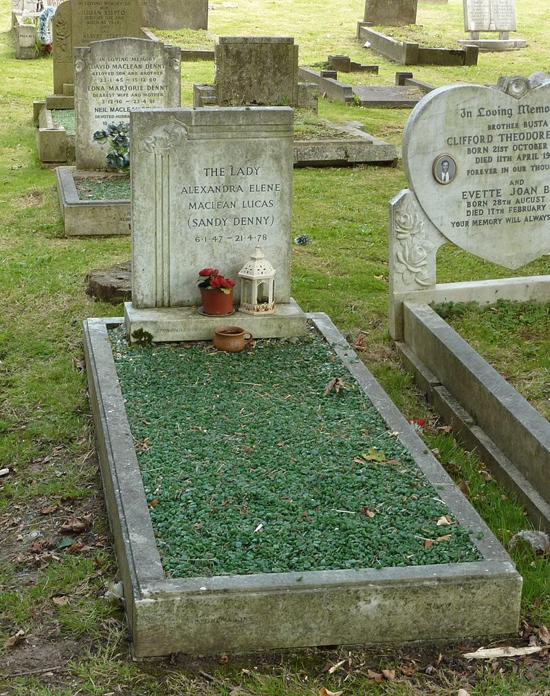 A grave covered with emerald-like gravel, with a granite headstone, surrounded by other graves