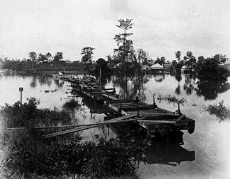 Ipswich and Rosewood railway line - Makeshift bridge of railway wagons during the 1890 flood between Milton and Auchenflower to allow passengers to reach the city. This photograph was taken in the vicinity of Eagle Terrace looking towards Park Road. (Description supplied with photograph.)