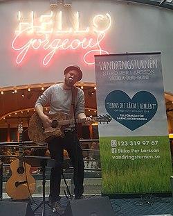 Stiko Per Larsson med guitar under et neonskilt med teksten Hello Gorgeous.