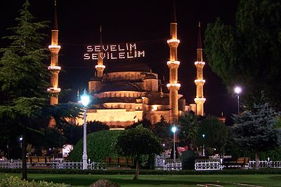 "Traditional Bayram Wishes from the Istanbul Metropolitan Municipality, stating ""Love and Be Loved"", in the form of mahya lights stretched across the minarets of the Blue Mosque in Istanbul, Turkey"