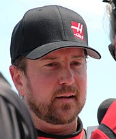 A man in his late thirties wearing a black baseball cap with the team logo on its left. He is being interviewed by another person for the press.