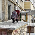 The old lady removes snow from the roof (Koryazhma).jpg