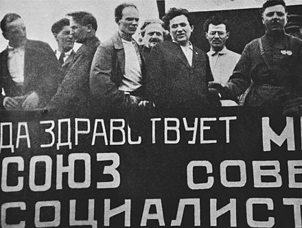 The red banner from the Commune brought to Moscow by French communists in June 1924 Kliment Voroshilov is at right, Grigory Zinoviev third from right, Avel Enukidze fourth, and Nikolay Antipov fifth. The red banner from the Commune, brought to Moscow by French communists.jpg