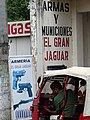 Tuk-Tuk Driver outside Guns & Munitions Store - Rio Dulce - Izabal - Guatemala (15886301432).jpg