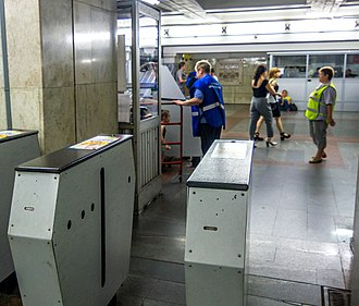 Fare evasion - Ticket inspector and guard watching for turnstiles in Moscow Metro