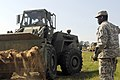 U.S. Army Pfc. Christopher Greene, a horizontal construction engineer assigned to the 1782nd Engineer Company, South Carolina Army National Guard, operates a scoop loader to clear an area for heavy vehicles to 130518-Z-ID851-001.jpg
