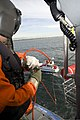 U.S. Coast Guard Petty Officer 2nd Class Miguel Arellano, an aviation maintenance technician, operates the hoist on an MH-65C Dolphin helicopter during training operations off the coast of Venice, Calif., Jan 120124-G-MR731-021.jpg