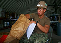 U.S. Navy Builder 3rd Class Edward Prejula, assigned to Diego Garcia Detachment, Naval Mobile Construction Battalion 3, sorts through stowed packaging in the Materials Liaisons Office while performing 130811-N-ZZ000-002.jpg