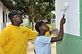 U.S. Navy Chief Warrant Officer 4 Ronald McMiller helps a student roll the last bit of paint on an exterior wall of the Integracao Infantil Cristo Vida school in Nacala, Mozambique, June 20, 2012 120620-N-UG232-222.jpg