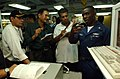 US Navy 041005-N-3503M-004 Electrician's Mate 3rd Class Tamfu Fomuso describes to Indian media how the engineering department operates while underway.jpg
