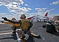 US Navy 060308-N-1045B-015 Lt. Gregory Petrovic and Michael Simson, signal to the deck edge operator that the T-45A Goshawk is ready to be launched.jpg