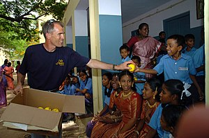 USS Nimitz - Lt. Cmdr. David Bynum, a Navy chaplain aboard Nimitz, passes out happy face sponge balls to the students of CSI High School for the Deaf in Chennai India during a community relations visit in July 2007.