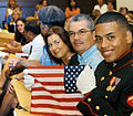 US Navy 070727-N-8047K-001 Lance Cpl. Luis Camacho, a legalman at Naval Legal Services Office Central, aboard Naval Air Station Pensacola, holds up the American flag that was given to him during a naturalization ceremony.jpg