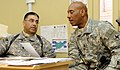 US Navy 081222-N-0000X-001 Army Lt. Col. Leo Griego, left, from Las Vegas, N.M., discusses ways to improve the accountability process of Afghanistan National Police assets with new command 1st Sgt. Senior Chief Ernest Edwards.jpg