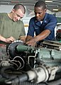 US Navy 090420-N-9950J-066 Marine Private 1st Class Joshua Huitt, from Houston, and Aviation Support Equipment Technician 3rd Class Justin Wright, from Chicago, replace the filter on a tractor.jpg