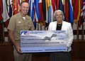 US Navy 090723-N-XXXXH-001 Adm. Mark Fitzgerald, Commander, U.S. Naval Forces Europe-Commander, U.S. Naval Forces Africa receives a check for $44,473.90 from Renee S. Acosta, President and CEO of Global Impact.jpg