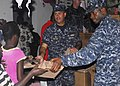 US Navy 100119-N-5244H-040 Cmdr. George Doyon, left, commanding officer of the amphibious dock landing ship USS Carter Hall (LSD 50), and Sailors assigned to Carter Hall distribute meals-ready-to-eat.jpg