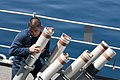 US Navy 110403-N-RC734-030 Cryptologic Technician (Technical) 3rd Class Hermenegildo Salas removes a chaff canister from the launcher aboard the am.jpg