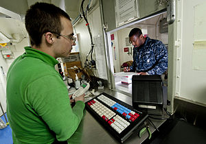 US Navy 111227-N-OY799-209 Logistics Specialist 3rd Class Joel Dunbar, from Boulder City, Nev., assists Aviation Ordnanceman Airman Eric Terrell, f.jpg