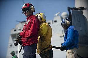 US Navy 120103-N-PB383-516 Aviation Ordnanceman 2nd Class Michael Beebe mans a fire hose during a flight deck firefighting exercise aboard the amph.jpg