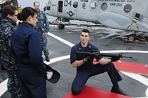 US Navy 120204-N-WV964-005 A Sailor answers questions about gun safety before a small arms shoot.jpg