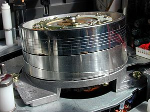 Helical scan - The head drum of a Hi-Fi NTSC VHS VCR; three of the six heads face the reader. The helical path of the tape around the drum can clearly be seen.