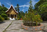 Vat Pa Phai temple in its garden with orange marigold, clouds and blue sky, in Luang Prabang Laos.jpg