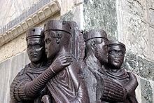 Sculpture située au coin d'un bâtiment aux murs en marbre représentant quatre hommes portant des toges et des épées. Les statues sont quasiment identiques et regroupées par deux.