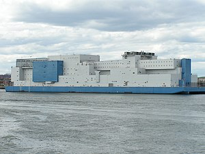 Vernon C. Bain Correctional Center - The blue and white barge as seen from Long Island Sound with the outdoor recreation area to the left and the gym in the center