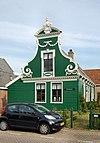 foto van Houten huis met rijk versierd voorschot in Lodewijk XVI-stijl