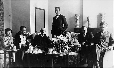 Wittgenstein sitting with his friends and family in Vienna. Marguerite Respinger sits at the end of the left and the sculpture he made of her sits behind him on the mantel-place