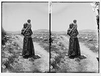 Woman holding child, standing in road LOC matpc.06319.jpg