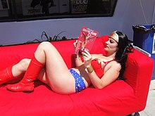 A woman dressed as Wonder Woman reclines on a red sofa with a red comic book.